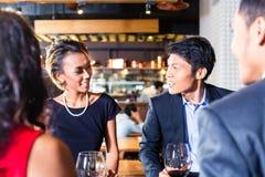 Amis asiatiques célébrant dans le restaurant Image libre de droits