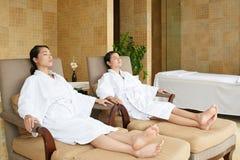 Amis asiatiques détendant dans le salon de station thermale Image stock