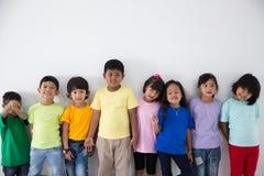 Amis asiatiques d'enfant utilisant le T-shirt coloré Photo stock