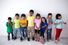 Amis asiatiques d'enfant utilisant le T-shirt coloré Photo libre de droits