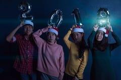 Amis asiatiques de groupe les jeunes tenant les mots 2018 font la fête ensemble le ce Photographie stock libre de droits