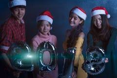Amis asiatiques de groupe les jeunes tenant les mots 2018 font la fête ensemble le ce Image stock
