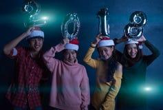 Amis asiatiques de groupe les jeunes tenant les mots 2018 font la fête ensemble le ce Image libre de droits