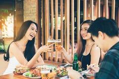 Amis asiatiques de Teeneger faisant tinter des verres tout en appréciant un evenin Images libres de droits