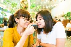Amis asiatiques féminins de sourire tenant des tasses de café tout en parlant b Images stock