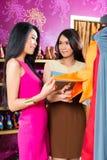 Amis asiatiques faisant des emplettes dans le magasin de mode Photographie stock libre de droits