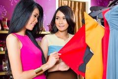 Amis asiatiques faisant des emplettes dans le magasin de mode Images libres de droits