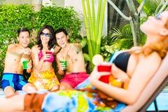 Amis asiatiques faisant la fête à la réception au bord de la piscine dans l'hôtel Images libres de droits