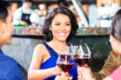 Amis asiatiques grillant avec du vin Image stock