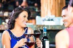 Amis asiatiques grillant avec du vin Image libre de droits