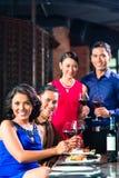 Amis asiatiques grillant avec du vin dans le restaurant Photo libre de droits