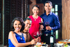 Amis asiatiques grillant avec du vin dans le restaurant Photo stock