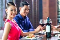Amis asiatiques grillant avec du vin dans le restaurant Photos stock