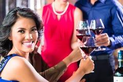 Amis asiatiques grillant avec du vin dans le restaurant Photographie stock libre de droits