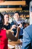 Amis asiatiques grillant avec le vin rouge dans la barre Photos stock