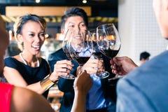 Amis asiatiques grillant avec le vin rouge dans la barre Image libre de droits