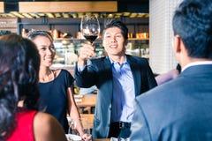Amis asiatiques grillant avec le vin rouge dans la barre Photo stock