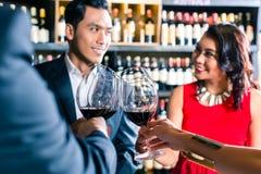 Amis asiatiques grillant avec le vin rouge dans la barre Image stock