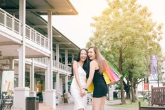 Amis asiatiques heureux marchant et faisant l'achat ensemble dehors Photographie stock libre de droits