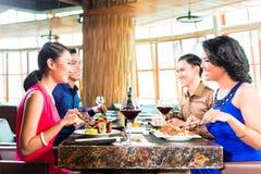 Amis asiatiques mangeant dans le restaurant Photographie stock libre de droits