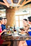 Amis asiatiques mangeant dans le restaurant Photos libres de droits