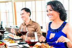 Amis asiatiques mangeant dans le restaurant Image libre de droits
