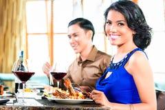 Amis asiatiques mangeant dans le restaurant Images libres de droits