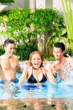 Amis asiatiques nageant dans la piscine Photo libre de droits