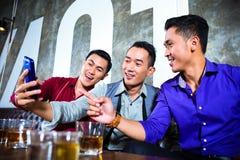Amis asiatiques prenant des photos ou des selfies dans la boîte de nuit de fantaisie Image libre de droits