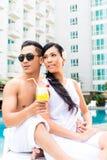 Amis asiatiques s'asseyant par la piscine d'hôtel Image stock
