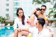 Amis asiatiques s'asseyant par la piscine d'hôtel Photographie stock