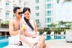 Amis asiatiques s'asseyant par la piscine d'hôtel Images stock