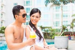 Amis asiatiques s'asseyant par la piscine d'hôtel Images libres de droits