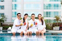 Amis asiatiques s'asseyant par la piscine d'hôtel Photos stock