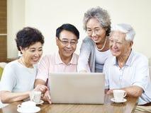 Amis asiatiques supérieurs se réunissant à la maison Photo stock