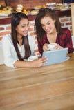 Amis assez féminins appréciant un café utilisant le PC de comprimé Photo libre de droits