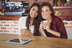 Amis assez féminins appréciant un café utilisant le PC de comprimé Photographie stock