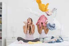 Amis assez féminins avec des vêtements sur le lit Photo stock