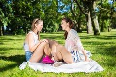 Amis assez féminins détendant dans parler de parc Photo stock
