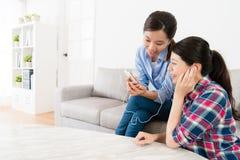 Amis assez féminins heureux utilisant des écouteurs Image stock