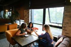 Amis assez féminins parlant au café et à l'aide du smartphone, café potable Image libre de droits
