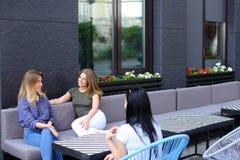 Amis assez féminins parlant au café et s'asseyant sur le sofa Photographie stock