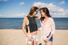 Amis assez féminins regardant l'un l'autre riant sur la plage Images libres de droits