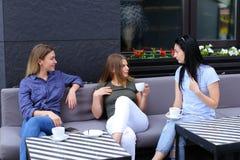 Amis assez féminins riant et parlant au café, café potable Images libres de droits