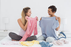 Amis assez féminins sélectionnant des vêtements dans le lit Photos libres de droits
