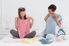 Amis assez féminins sélectionnant des vêtements dans le lit Images stock