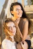 Amis assez féminins s'asseyant sur les escaliers en bois Photographie stock libre de droits