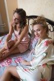 Amis assez jeunes causant sur le lit à la maison dedans Image stock