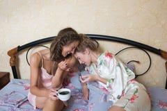 Amis assez jeunes causant sur le lit à la maison dedans Image libre de droits