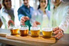 Amis atteignant vers l'échantillonneur de bière Photo stock